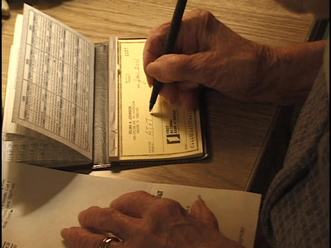 A senior citizen writes a check to pay a bill Stock Video Footage
