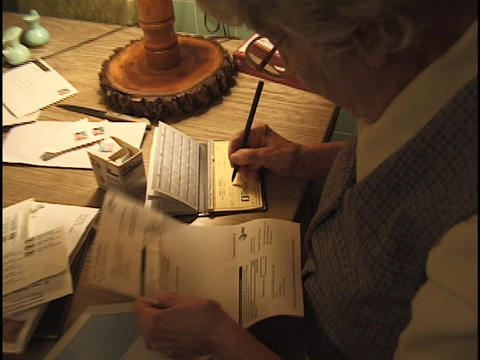 A senior citizen writes a check to pay a bill Footage