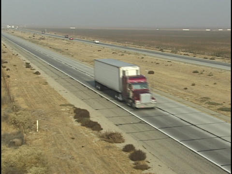 Traffic drives on an interstate in the desert Stock Video Footage