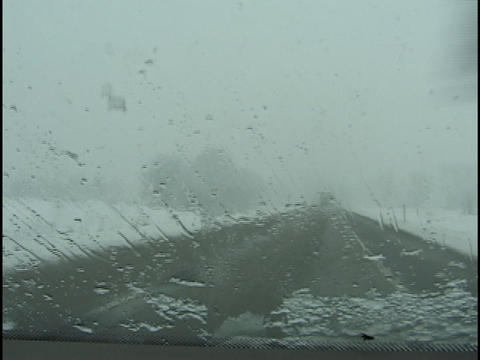 Windshield wipers clear snow from a windshield in winter... Stock Video Footage