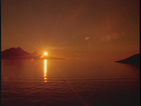 The midnight sun shines above the ocean waters in this... Stock Video Footage
