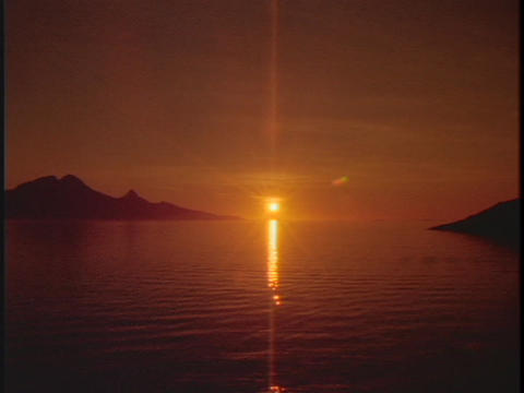 The midnight sun shines above the ocean waters in this time lapse shot Footage