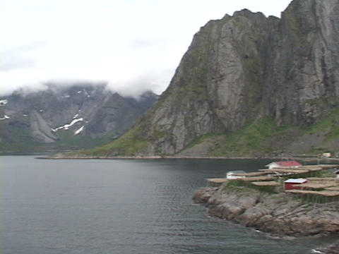 A small fishing village nestles on the edge of a fjord in... Stock Video Footage
