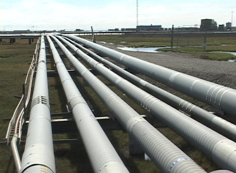Pan-left across rows of pipes to Halliburton facility buildings Footage
