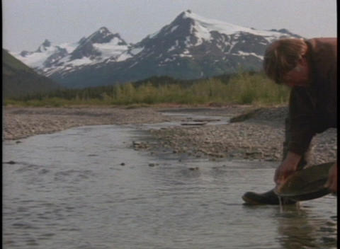 A prospector pans for gold in a mountain stream Stock Video Footage