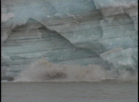 Ice breaks off of a glacier and falls into the ocean Stock Video Footage