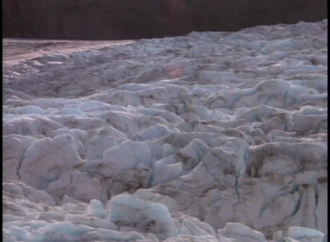 A muddy river flows past an ice and snow field Footage