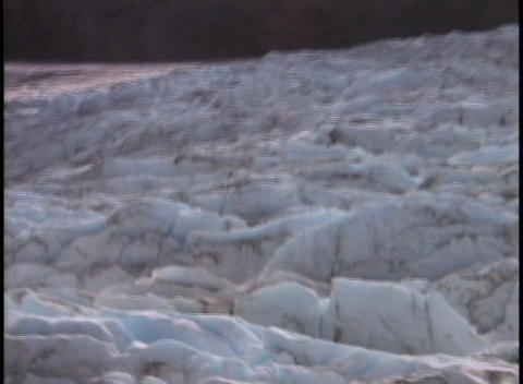 A muddy river flows past an ice and snow field Stock Video Footage