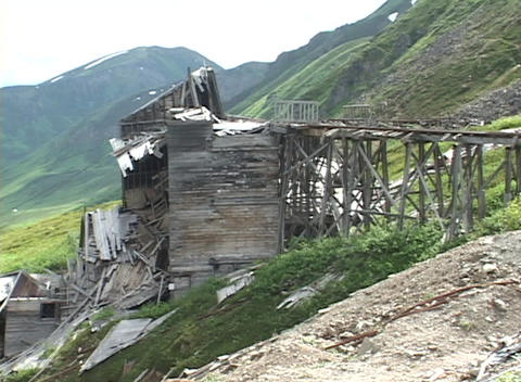 A collapsed wooden bridge surrounds part of a mountain Footage