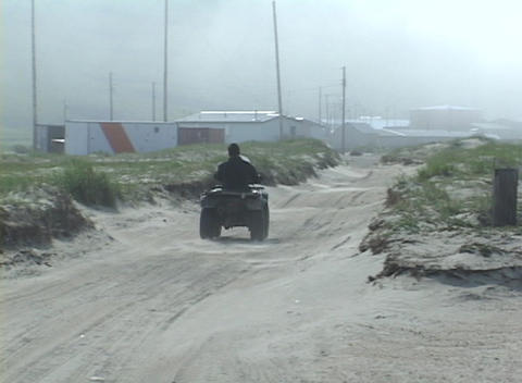 A native Alaskan drives his ATV into a windy town in the... Stock Video Footage