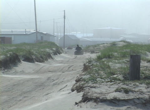 A native Alaskan drives his ATV into a windy town in the Aleutian Islands Footage