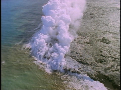 Steam rises as lava flows into the sea in Hawaii Stock Video Footage