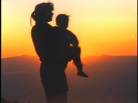 A woman holds a child and they observe a landscape Stock Video Footage