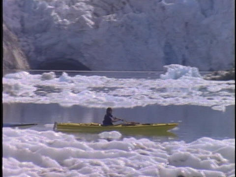 Kayakers paddle through a glacial bay Stock Video Footage