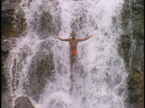 A man stands in a waterfall with outstretched arms Stock Video Footage