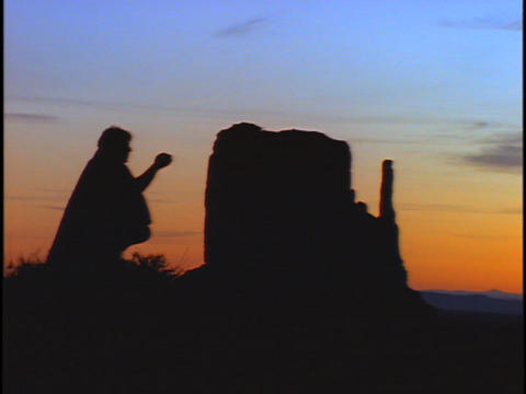A Native American prays near a rock formation Footage