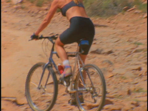 women ride mountain bikes along a desert trail Stock Video Footage