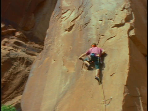 A young man scales a steep, rock face Footage