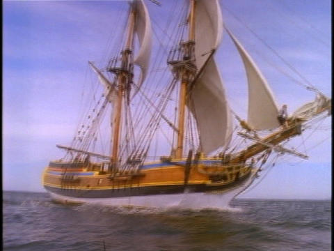 A sailor adjusts the rigging on a clipper ship at sea Stock Video Footage