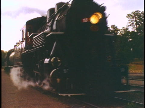 An old steam engine pulls passengers cars along a... Stock Video Footage