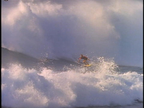 A surfer rides a huge wave then disappears in the surf Stock Video Footage
