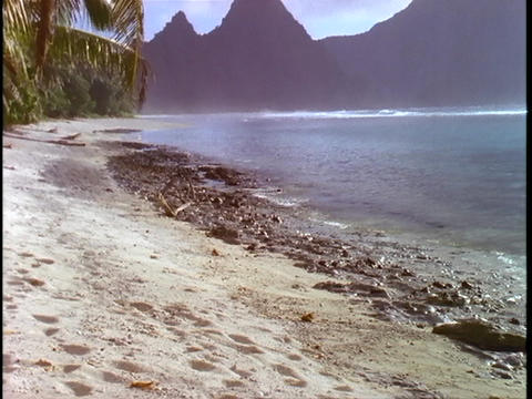 Gentle waves roll onto a tropical beach in American Samoa Stock Video Footage
