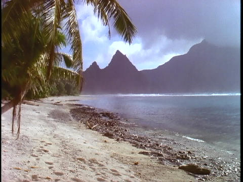Gentle waves roll onto a tropical beach in American Samoa Footage