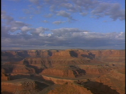 Clouds float over vast, red rock canyon lands Stock Video Footage