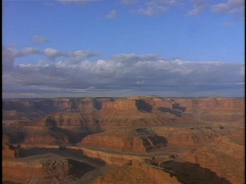Clouds float over vast, red rock canyon lands Footage