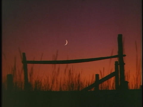 A crescent moon hangs above a rustic fence Footage