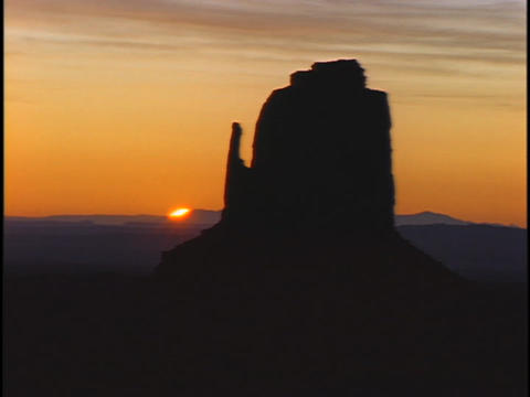 A geologic formation stands in silhouette above the horizon Footage
