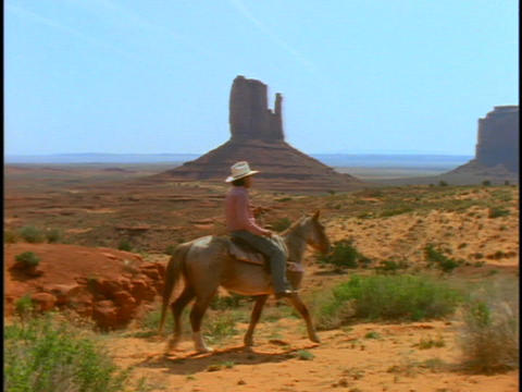 people ride horses through Monument Valley Stock Video Footage