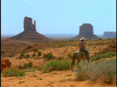 people ride horses through Monument Valley Footage