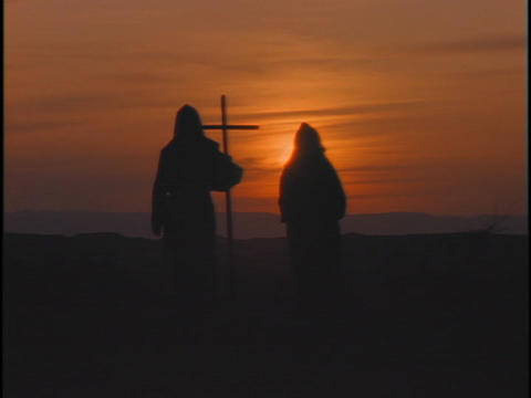 people in hooded robes walk and carry a cross Stock Video Footage