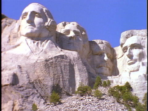 The massive, carved images of four American presidents rise against a blue sky at Mt. Rushmore Footage