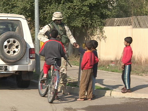 U.S. soldier talks to children on the street in Iraq Stock Video Footage