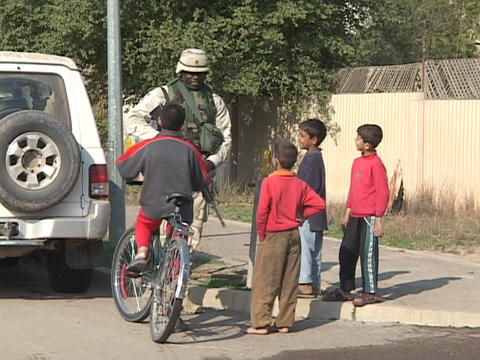 U.S. soldier talks to children on the street in Iraq Footage
