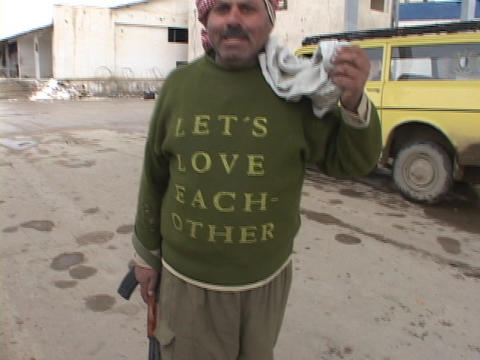 "An Iraqi man holding a rifle shows his shirt which says Lets Love Each Other""."" Footage"