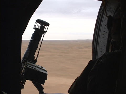A Black Hawk helicopter carrying soldiers flies over Iraq Stock Video Footage