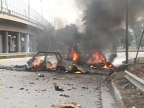 The remains of a car burn on the streets in Baghdad after a terrorist bomb blast Footage