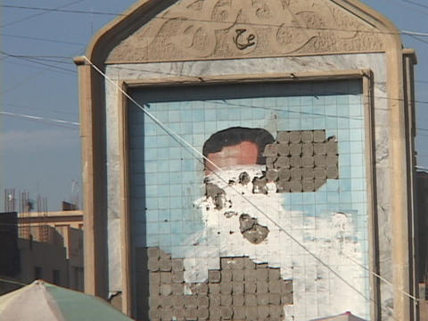 Crowds of people walk along the street in front of a destroyed mural of Saddam Hussein Footage