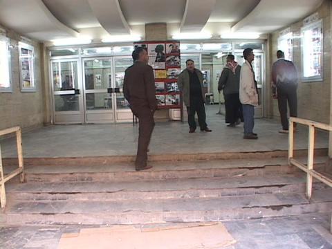 A group of men stand outside of an adult theater in Baghdad Stock Video Footage