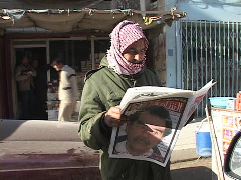 An Iraqi man reads a newspaper with a picture of Saddam Hussein on the cover Footage