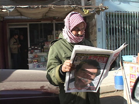 An Iraqi man reads a newspaper with a picture of Saddam... Stock Video Footage