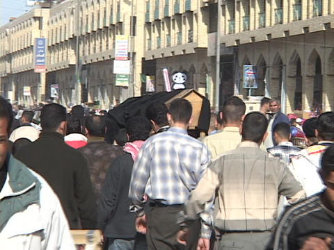 A funeral procession moves through a busy Baghdad street... Stock Video Footage