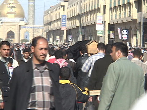 A funeral procession moves through a busy Baghdad street among crowds of Iraqis Footage
