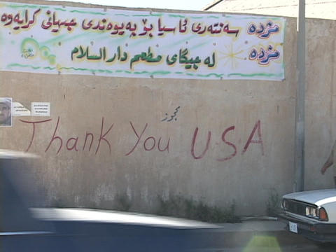 Cars and pedestrians pass by a thank you sign to the U.S.A. on a wall in Kurdistan, Iraq Footage