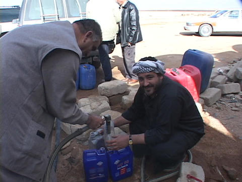 Iraqi citizens siphon gas during the war's fuel shortage Stock Video Footage