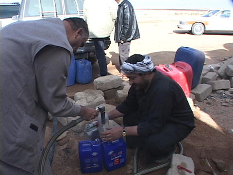 Iraqi citizens siphon gas during the war's fuel shortage Footage