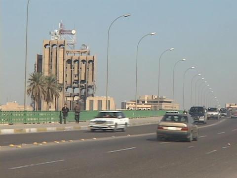 Iraqis jog near a damaged building of war-torn Baghdad, Iraq Stock Video Footage